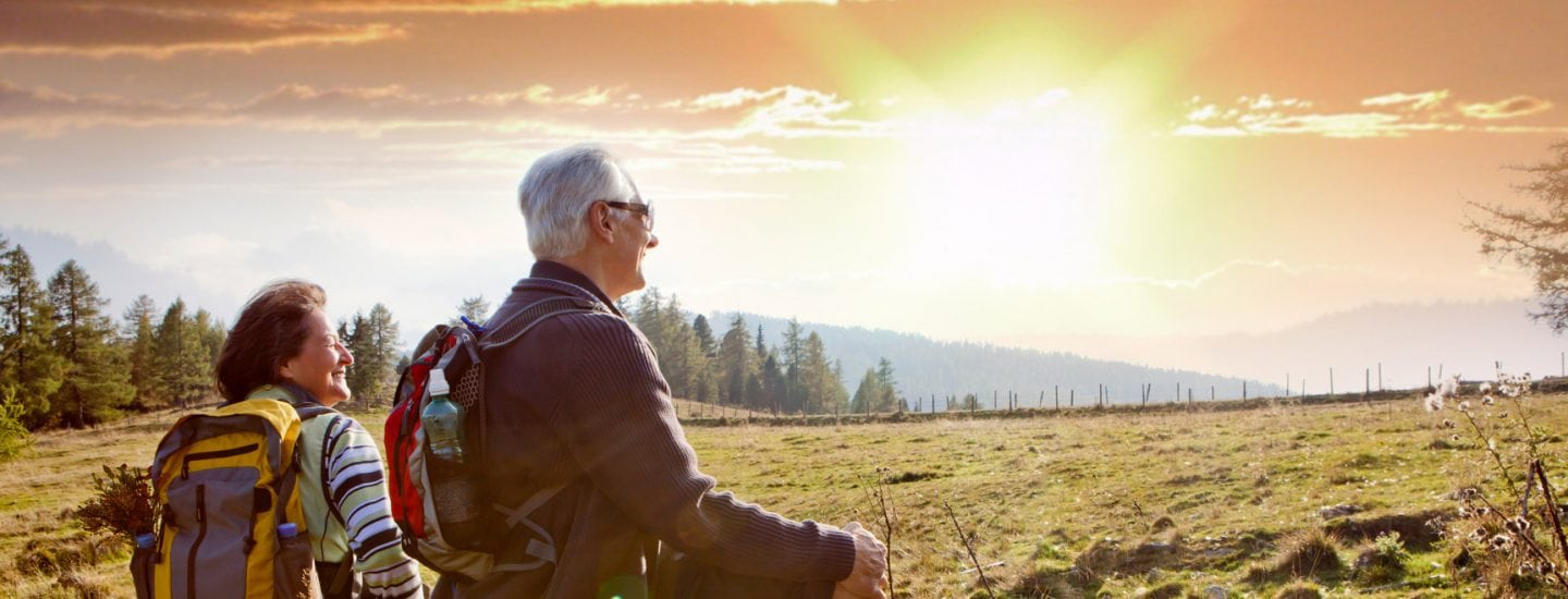 Travelling, elderly couple hiking on hilltop with sun in sky